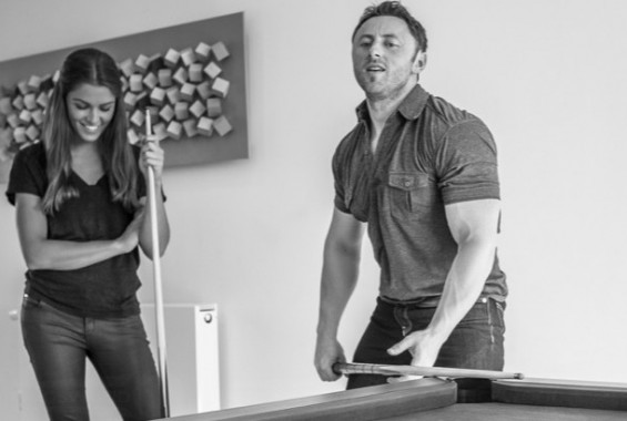 young couple playing pool at home